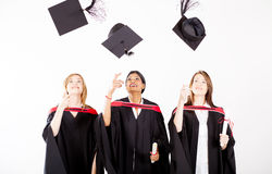 Graduates throwing graduation caps Stock Photography