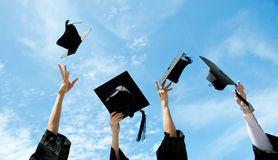 Graduates. Throwing graduation hats in the air Royalty Free Stock Photo