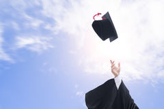 Graduates throwing graduation hats in the air Royalty Free Stock Image