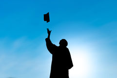 Graduates throwing hat on graduation day, silhouette. With blue sky Royalty Free Stock Image