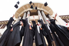 Graduates throwing hats. Group of happy graduates throwing graduation hats in the air celebrating stock images