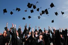 Graduates throwing mortarboards Stock Photo