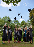 Graduates throwing  into the sky academic caps Royalty Free Stock Images
