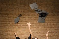 Graduates throwing their mortar boards Stock Photos