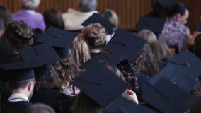 Graduates watching diploma awarding ceremony at university, higher education. Stock footage stock footage