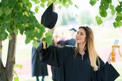 Graduatie: Student Standing With Diploma met erachter Vrienden stock foto's