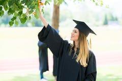 Graduatie: Student Standing With Diploma met erachter Vrienden royalty-vrije stock fotografie