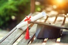 Graduatiehoed met leeswijzer, diploma met rood royalty-vrije stock afbeeldingen