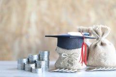 Graduatiehoed op de geldzak met bankbiljet op houten backgrou stock fotografie