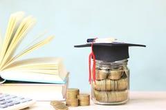 Graduatiehoed op de glasfles en boeken op witte achtergrond, die geld voor onderwijsconcept besparen stock foto's