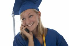 Graduating girl in gown on cell Royalty Free Stock Images