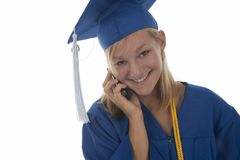 Graduating girl in gown on cell Royalty Free Stock Photography