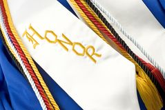 Graduating with Honors. A blue graduation gown with cords and the word Honors, horizontal full frame Stock Photo