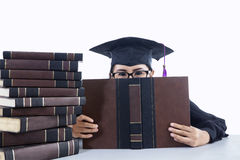 Graduating student girl covering her face on white background Stock Image