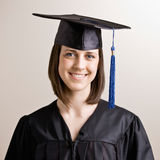 Graduating student wearing cap and gown Stock Images