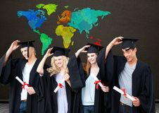 Graduating students under Colorful Map with blackboard background. Digital composite of Graduating students under Colorful Map with blackboard background Stock Photo