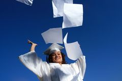 Graduation. Happy young graduate throwing out school papers, dusk sky behind Stock Photography