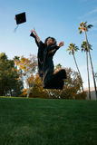 Graduation. Woman jumping for joy with her graduation gown and cap Stock Image
