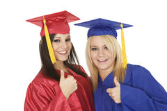 Caucasain girls wearing  gratuation gowns giving the thumbs up sign Stock Images