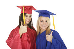 Caucasain girls wearing  gratuation gowns giving the thumbs up sign Royalty Free Stock Photo