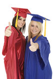 Caucasain girls wearing  gratuation gowns giving the thumbs up sign Stock Photos