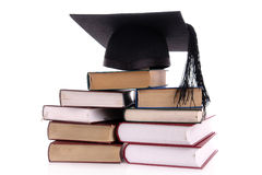 Graduation. Black graduation cap on pile of books over white Royalty Free Stock Photos