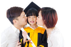 Graduation. Asian kindergarten child in graduation gown and mortarboard kissed by her parent during graduation Stock Photography
