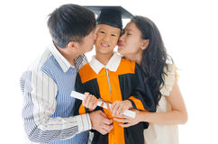 Graduation. Asian kindergarten child in graduation gown and mortarboard kissed by her parent during graduation Royalty Free Stock Photos