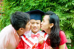 Graduation. Asian parent kiss their son on his kinder graduation day royalty free stock photography