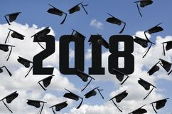 Graduation 2018 black hats in sky with clouds. Black graduation caps in blue sky with clouds for class of 2018 Royalty Free Stock Images