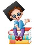 Graduation boy sitting on piles of books Royalty Free Stock Photo