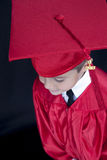 Graduation Boy. A young boy dressed in his graduation cap and gown royalty free stock photos