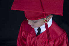 Graduation Boy. A young boy dressed in his graduation cap and gown stock images