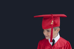 Graduation Boy. A young boy dressed in his graduation cap and gown royalty free stock photo