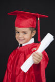 Graduation Boy. A young boy dressed in his graduation cap and gown stock photo