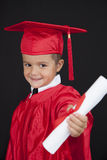 Graduation Boy. A young boy dressed in his graduation cap and gown stock image