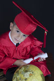 Graduation Boy. A young boy dressed in his graduation cap and gown holds his diploma. He is sitting next to a globe stock photo