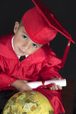 Graduation Boy. A young boy dressed in his graduation cap and gown holds his diploma. He is sitting next to a globe stock photography