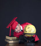 Graduation Boy. A young boy dressed in his graduation cap and gown holds his diploma. He is sitting next to a globe royalty free stock images