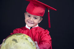 Graduation Boy. A young boy dressed in his graduation cap and gown holds his diploma. He is standing behind a globe stock photography