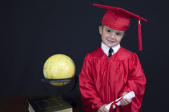Graduation Boy. A young boy dressed in his graduation cap and gown holds his diploma. He is standing next to a globe and books stock images
