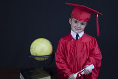 Graduation Boy. A young boy dressed in his graduation cap and gown holds his diploma. He is standing next to a globe and books royalty free stock photos