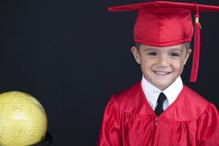 Graduation Boy. A young boy dressed in his graduation cap and gown holds his diploma. He is standing next to a globe and books stock image