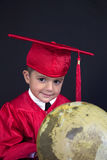 Graduation Boy. A young boy dressed in his graduation cap and gown holds his diploma. He is standing next to a globe and books royalty free stock photography