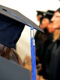 Graduation cap. With blue tassel detail. Female students in the background stock image
