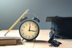 Graduation cap with alarm clock on wood board . royalty free illustration