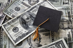 Graduation cap on assorted money Royalty Free Stock Photography