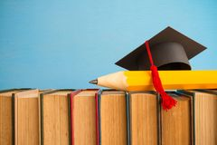 Graduation cap and big pencil over the books on blue wall backgr. Ound - Education concept Royalty Free Stock Images