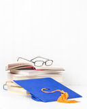 Graduation Cap and Books. Blue graduation cap and a pile of textbooks with reading glasses Stock Photo