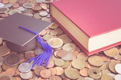 Graduation cap and books on many coins - Money saving for educat. Ion concept Stock Photography